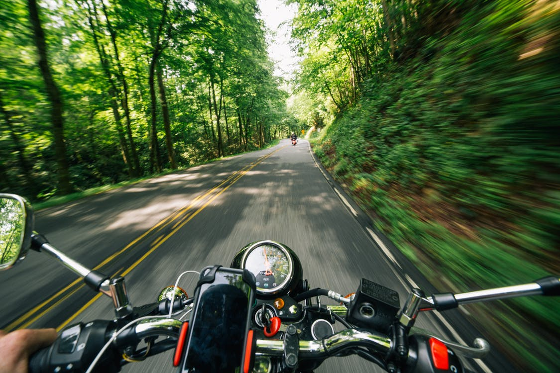 Photo of Person Riding Motorcycle on Road Between Trees