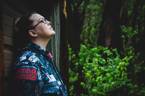 Photo of Woman Wearing Star Wars Jacket Leaning on Wall