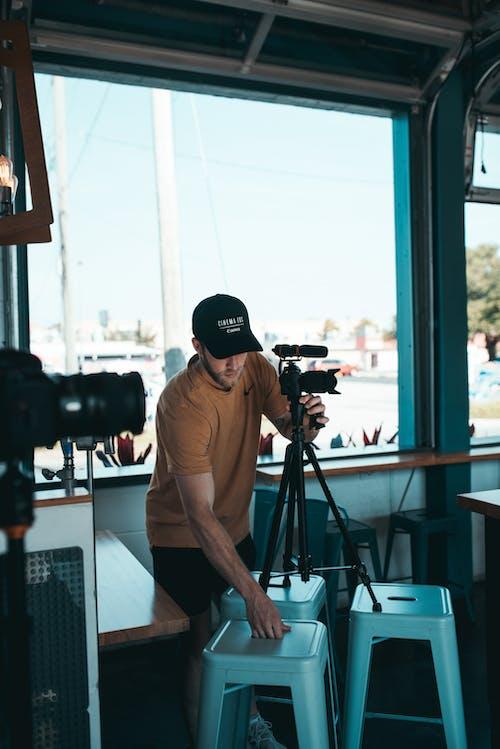 Man Fixing His Camera's Tripod