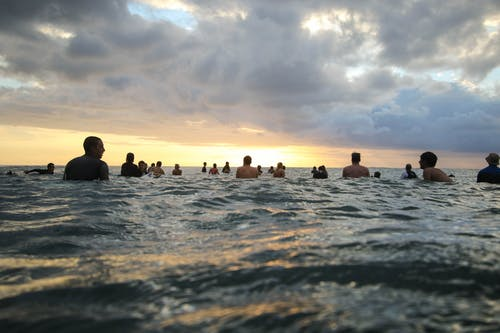 Photo of People In Ocean During Sunset