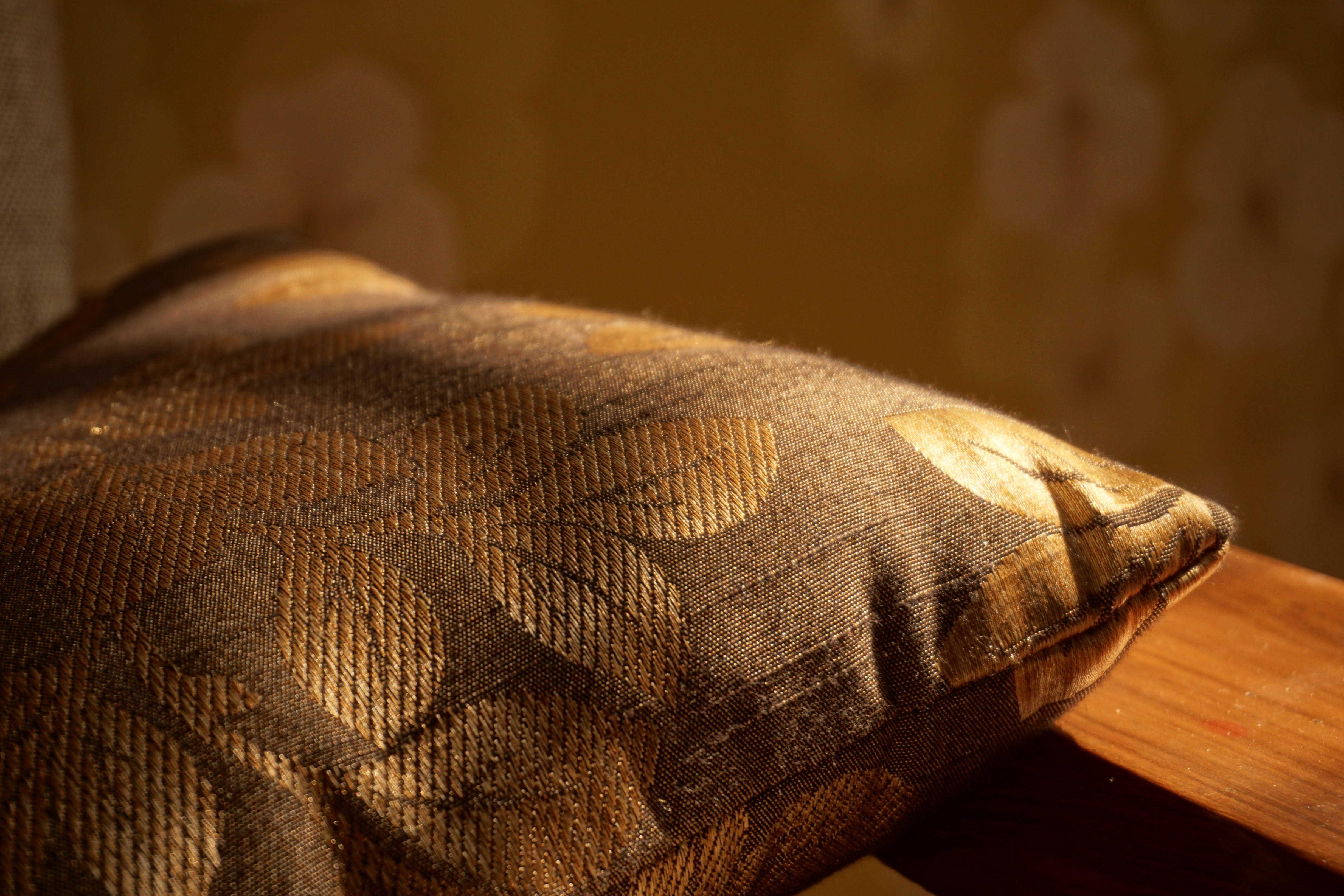 Gold Pillow on Brown Wooden Surface