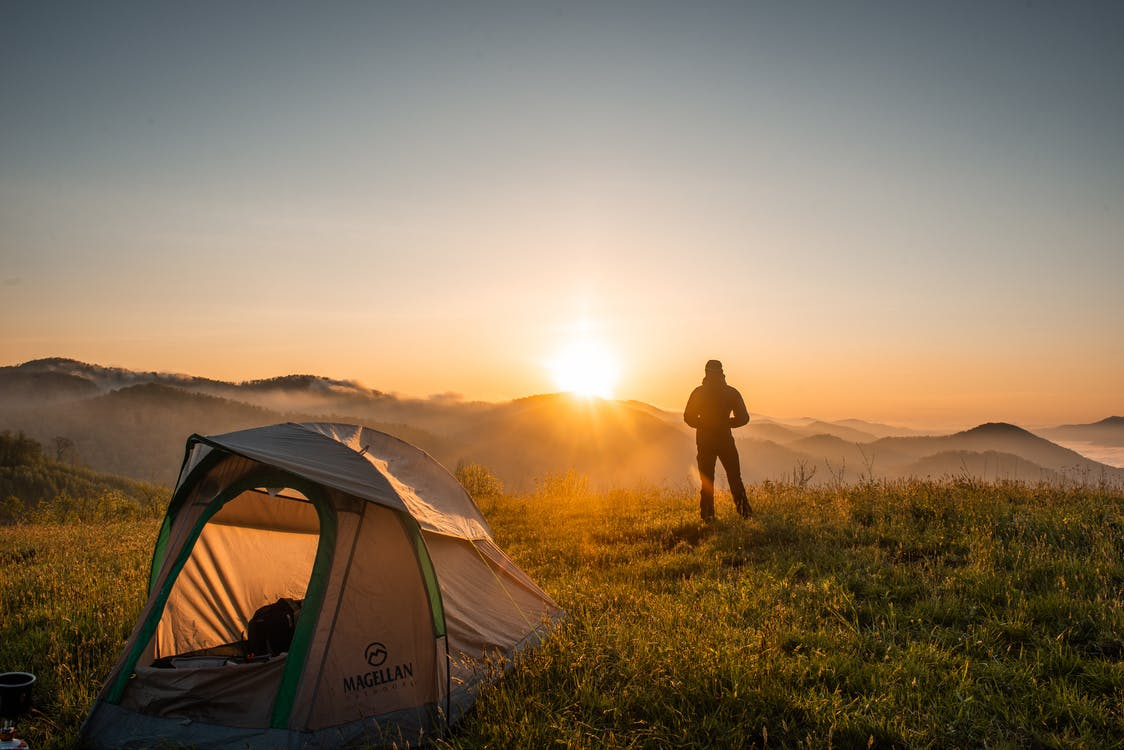 Silhouette of Person Standing Near Camping Tent