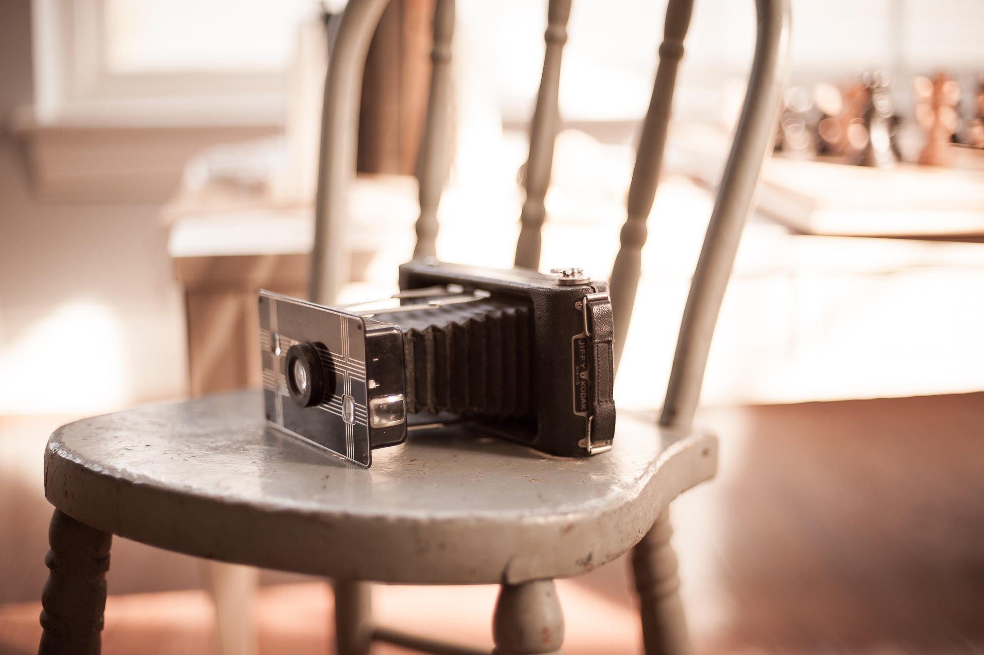 Black Folding Camera on Brown Chair on Focus Photo