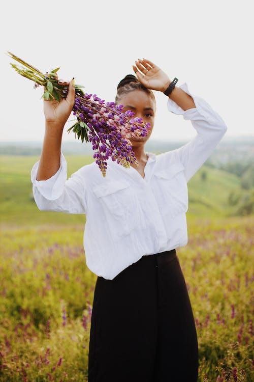 Photo of Woman Holding Purple Flowers