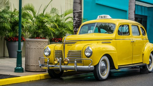 Photo of Yellow Taxi Parked Near Sidewalk