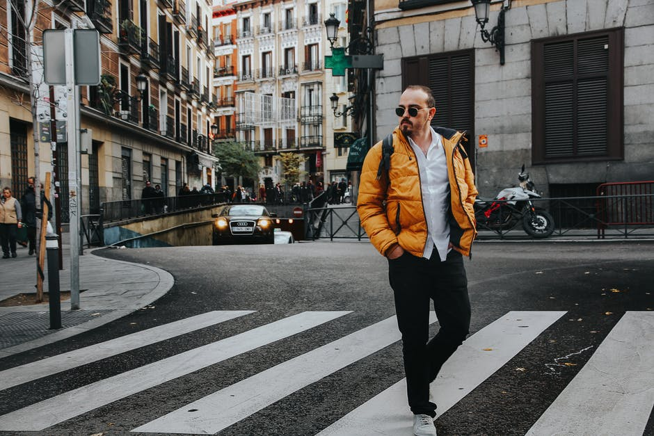 Photo of man walking on pedestrian crossing