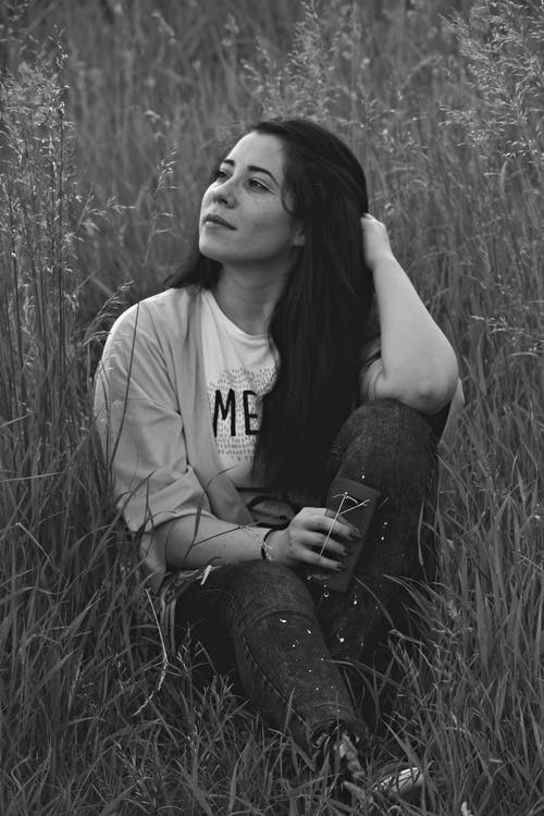Monochrome Photo of Woman Sitting on Grass