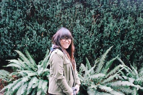 Mulher Vestindo Jaqueta Verde Ao Lado Da Planta De Samambaia De Boston