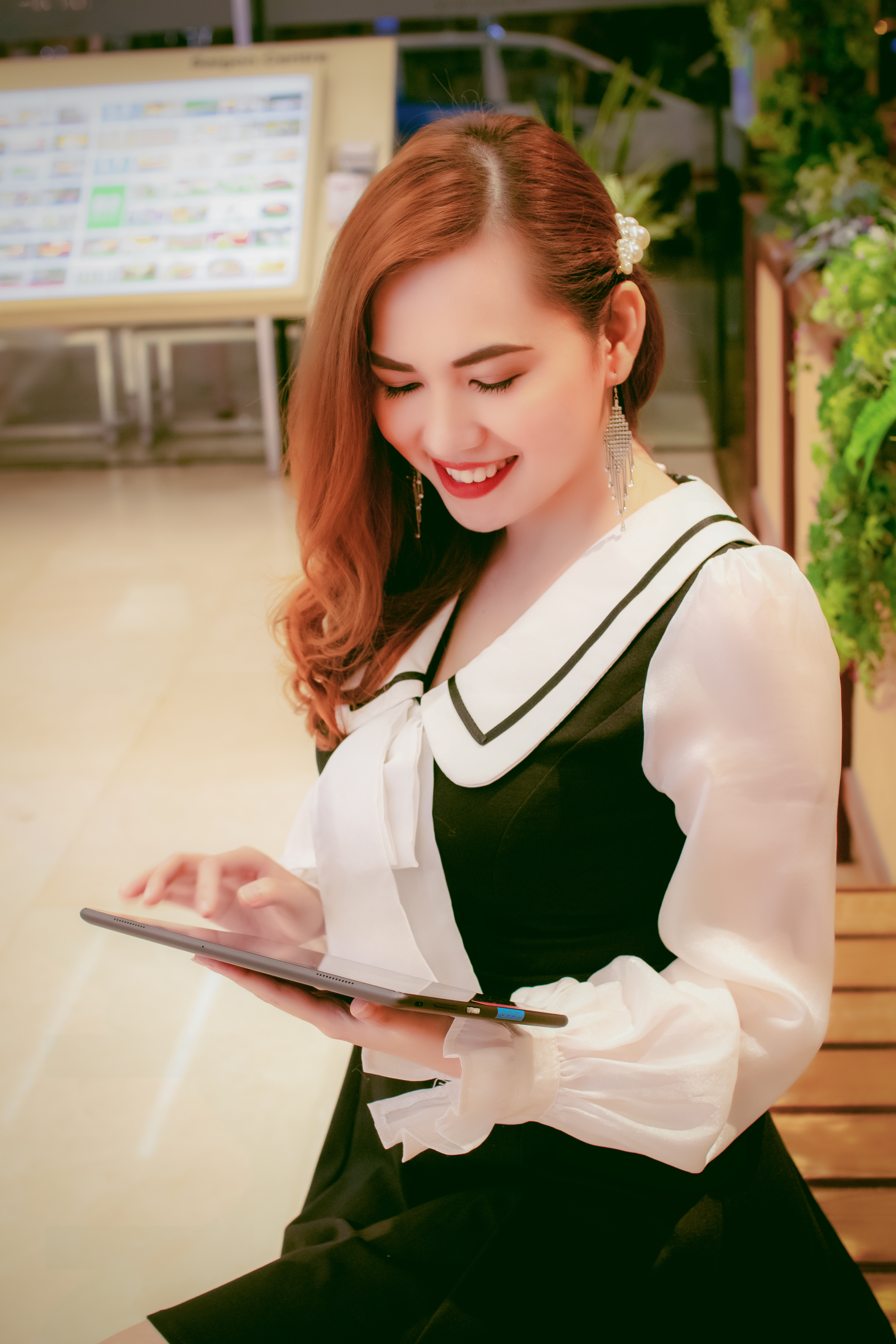 Photo of Smiling Woman in Black and White Outfit Standing While Using a Tablet
