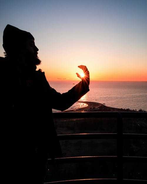 Forced Perspective Photography of Man Holding the Sun