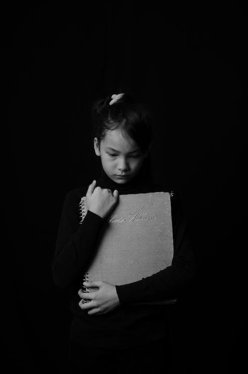Toddler Girl Holding Gray Book