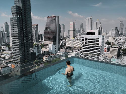 Man in Swimming Pool While Looking to Buildings