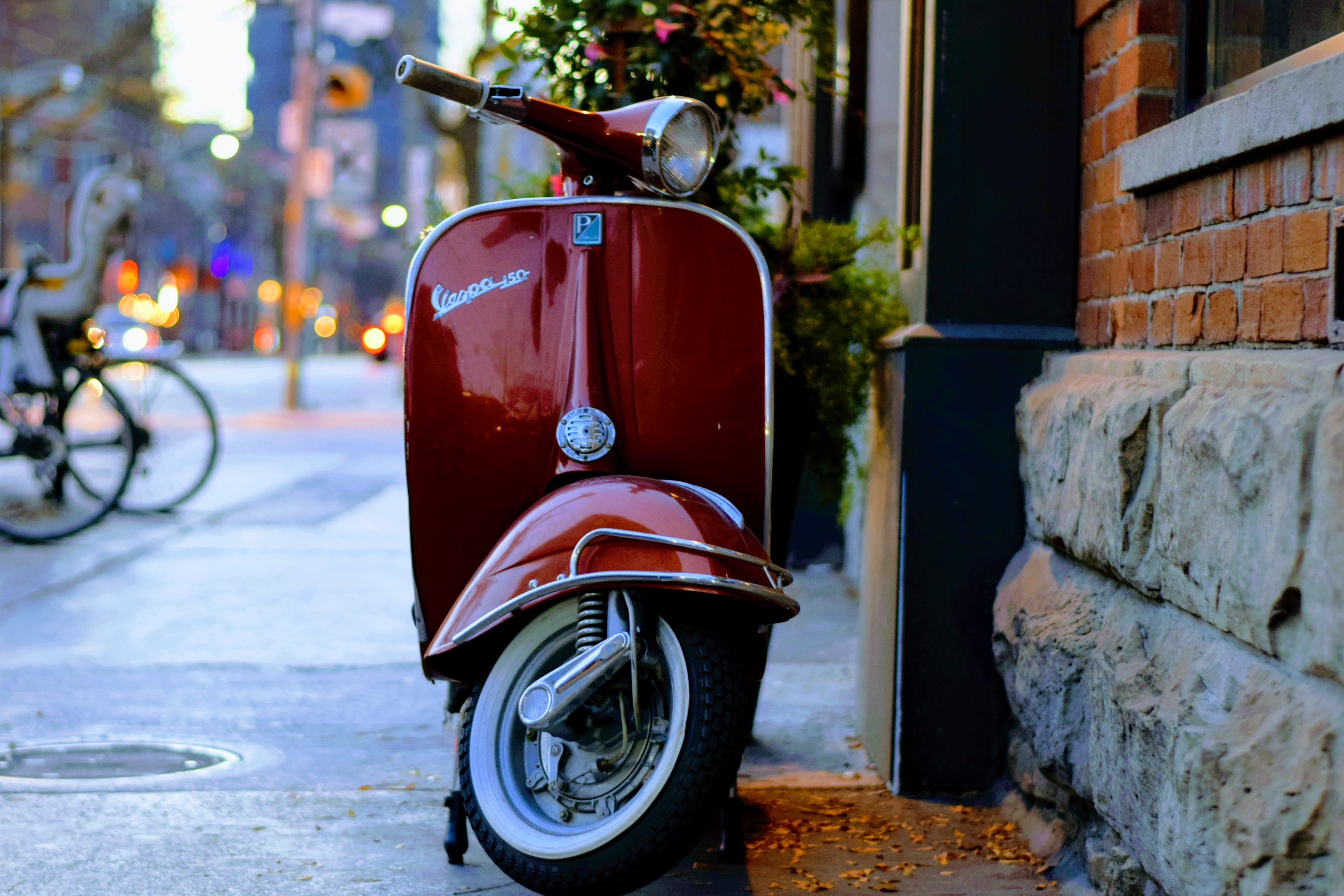 Red Piaggio Vespa Motor Scooter Parked Beside Gray and Red Concrete Building