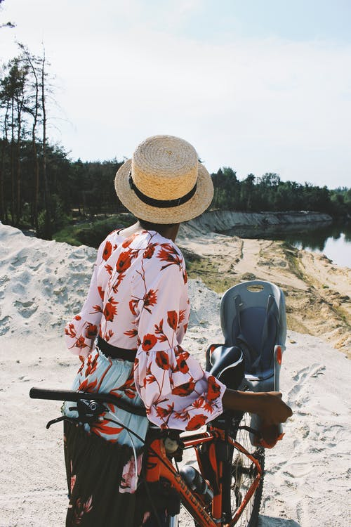 Woman Standing Beside Orange Mountain Bike
