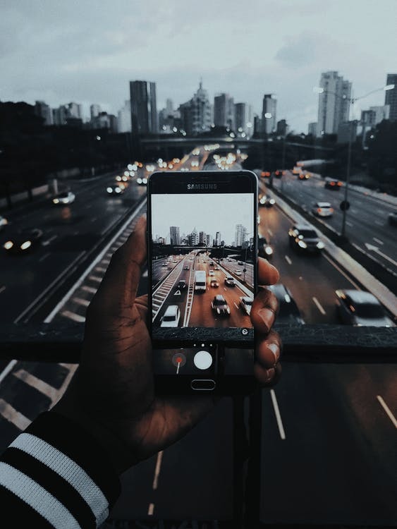Person Taking Photo of Cars on Road
