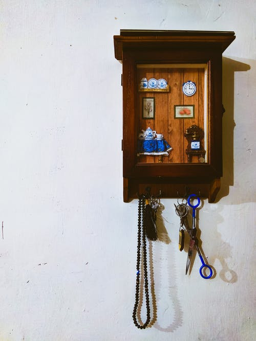 Black Prayer Beads and Blue Scissors Hanging on Wall Hook