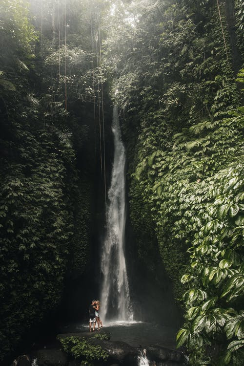 Woman and Man Standing Under Waterfall