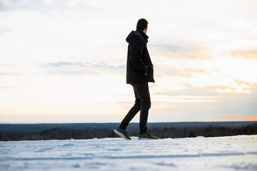 Man in Black Hooded Jacket and Pants Walking on Snow
