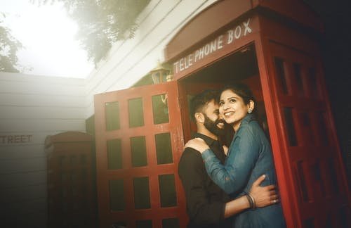 Photo of Smiling Couple Hugging While Standing By Red Telephone Booth