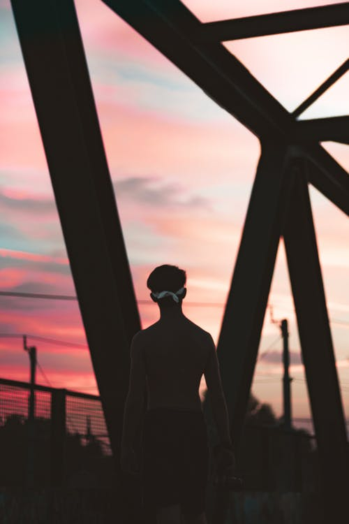 Topless Man Standing on Bridge during Sunset