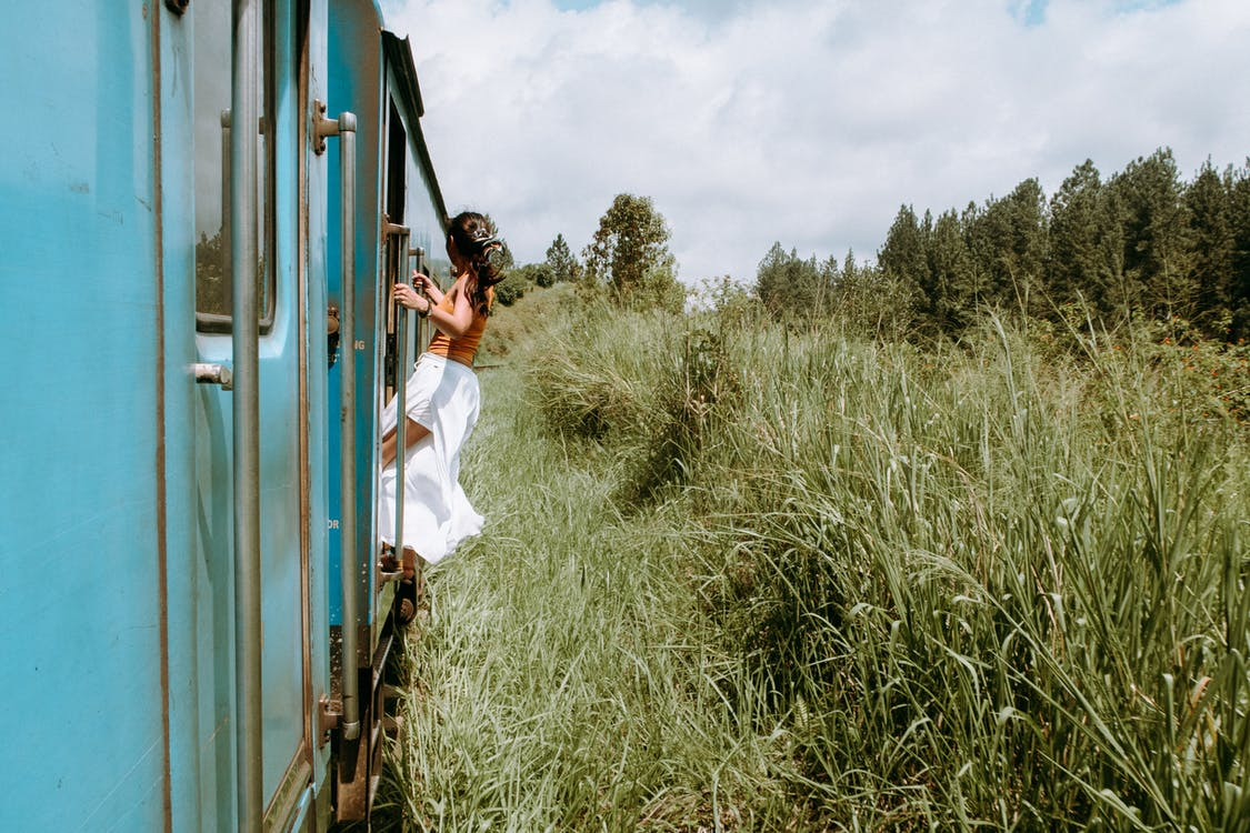 Photo of Woman in Brown Top and White Skirt Hanging from Train