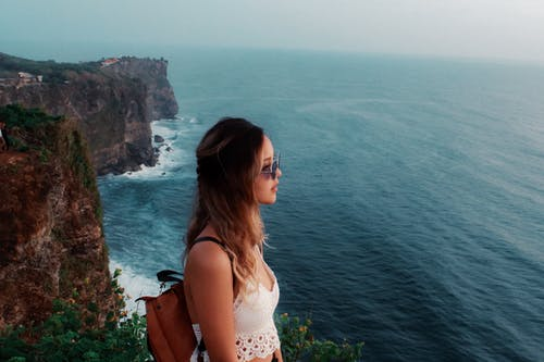 Woman Wearing White Cami Crop-top Standing on Rock Formation Near Body of Water