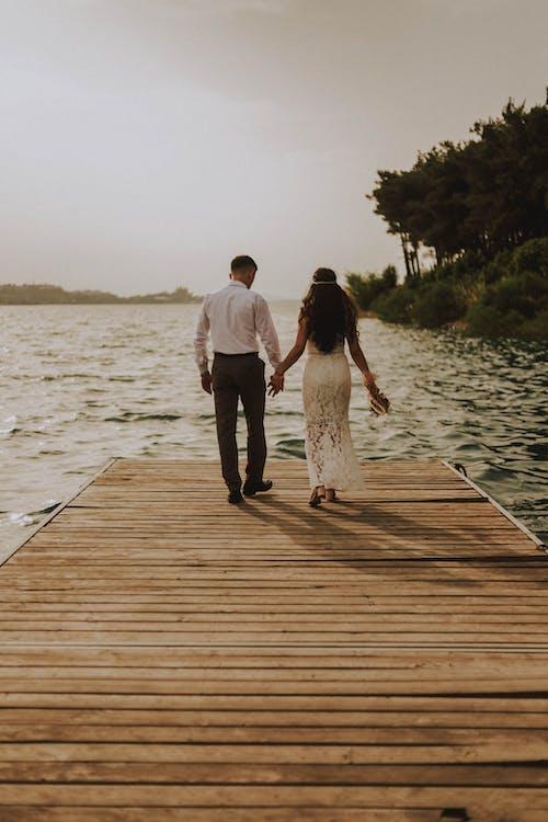 나무 판자에 서있는 커플의 사진