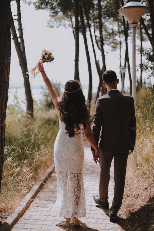 Photo of Couple Walking on Paved Pathway