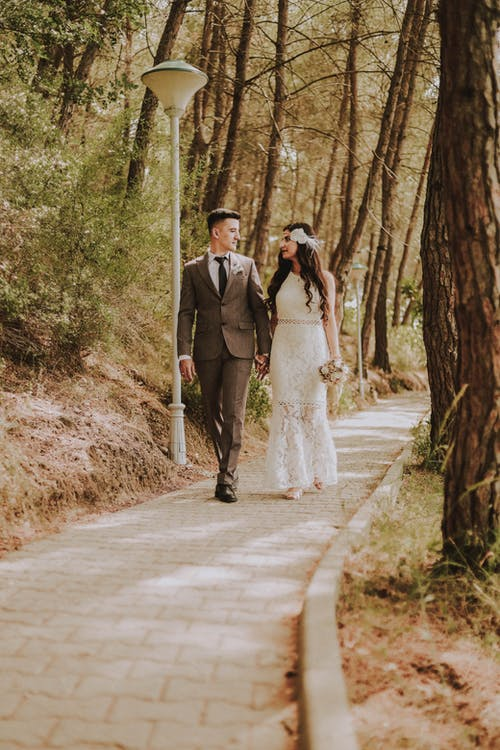 Photo of Married Couple Walking Near Tall Trees