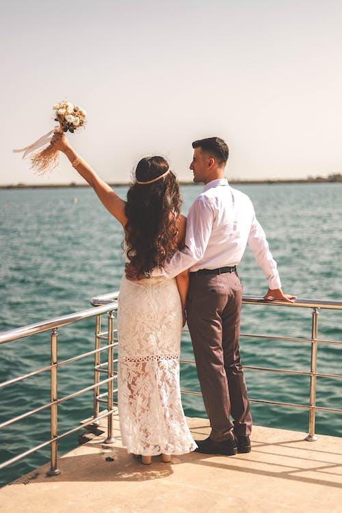 Photo of Married Couple Standing Near Metal Railings