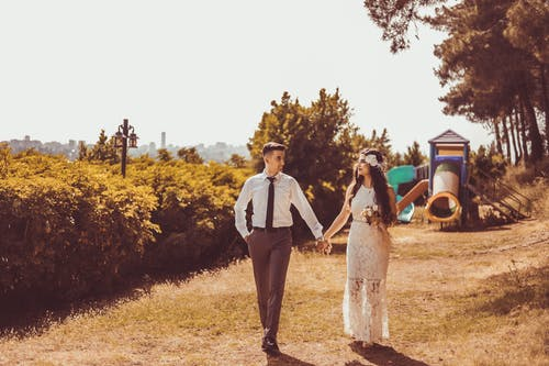 Photo of Couple Holding Hands While Walking
