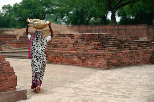 Foto De Mujer Caminando Mientras Lleva Una Cesta