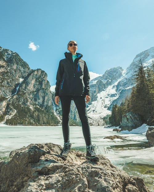 Woman Wearing Black While Standing on Rock