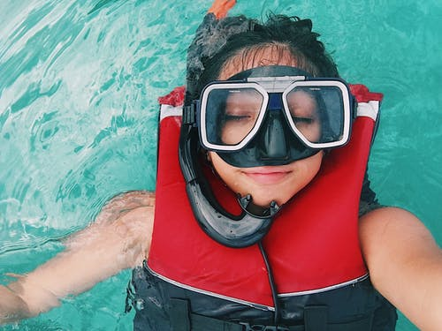 A person wearing red and black life vest and goggles while swimming