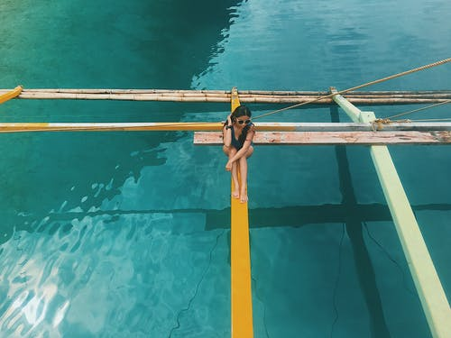 Photo of a Woman Sitting on Wooden Boat's Outrigger