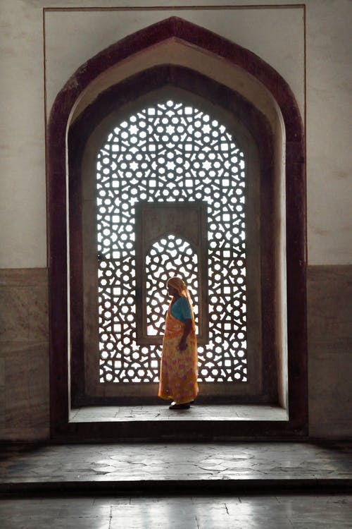 Woman Standing Near Mosaic Window