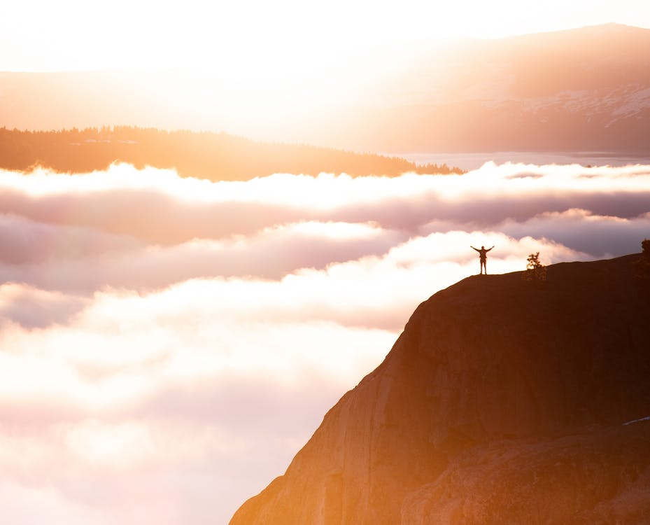 Photo of a Person Standing in Mountain