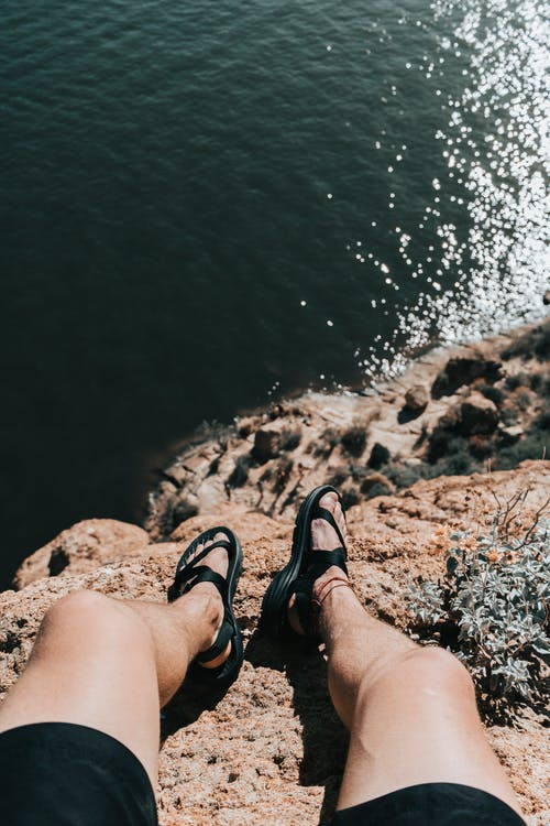 Faceless person resting on rocky cliff above ocean coast