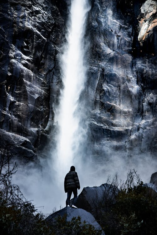 Man standing near a waterfall