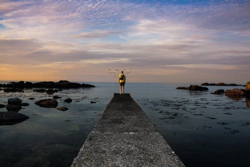 Photo of a Person Standing on Sea Dock