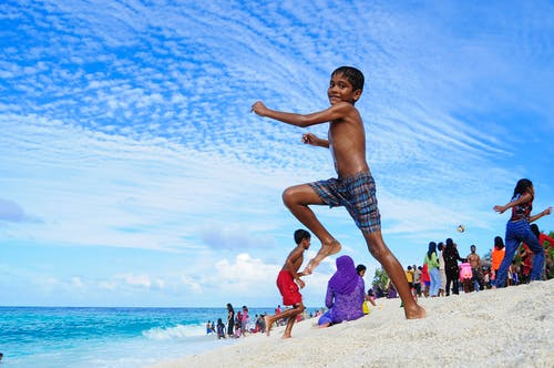 Boy Jumping on White Sand Near Ocean