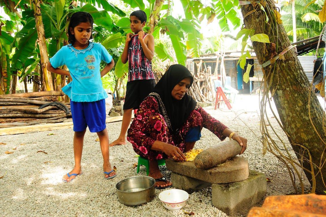 Girls Standing Behind Woman Crushing Food