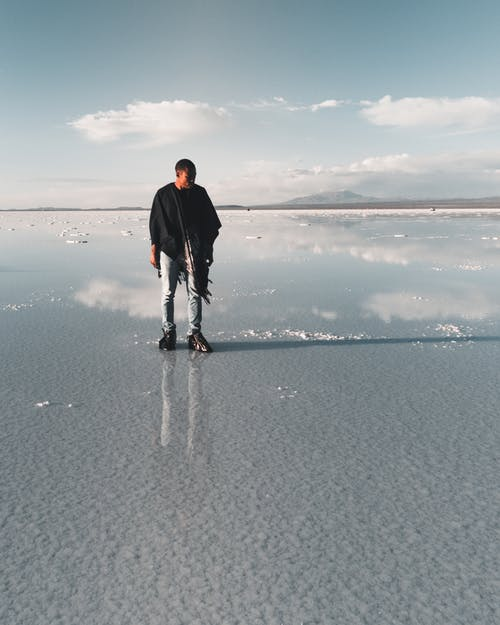 Photo of a Man Standing on Low Tide Seabed