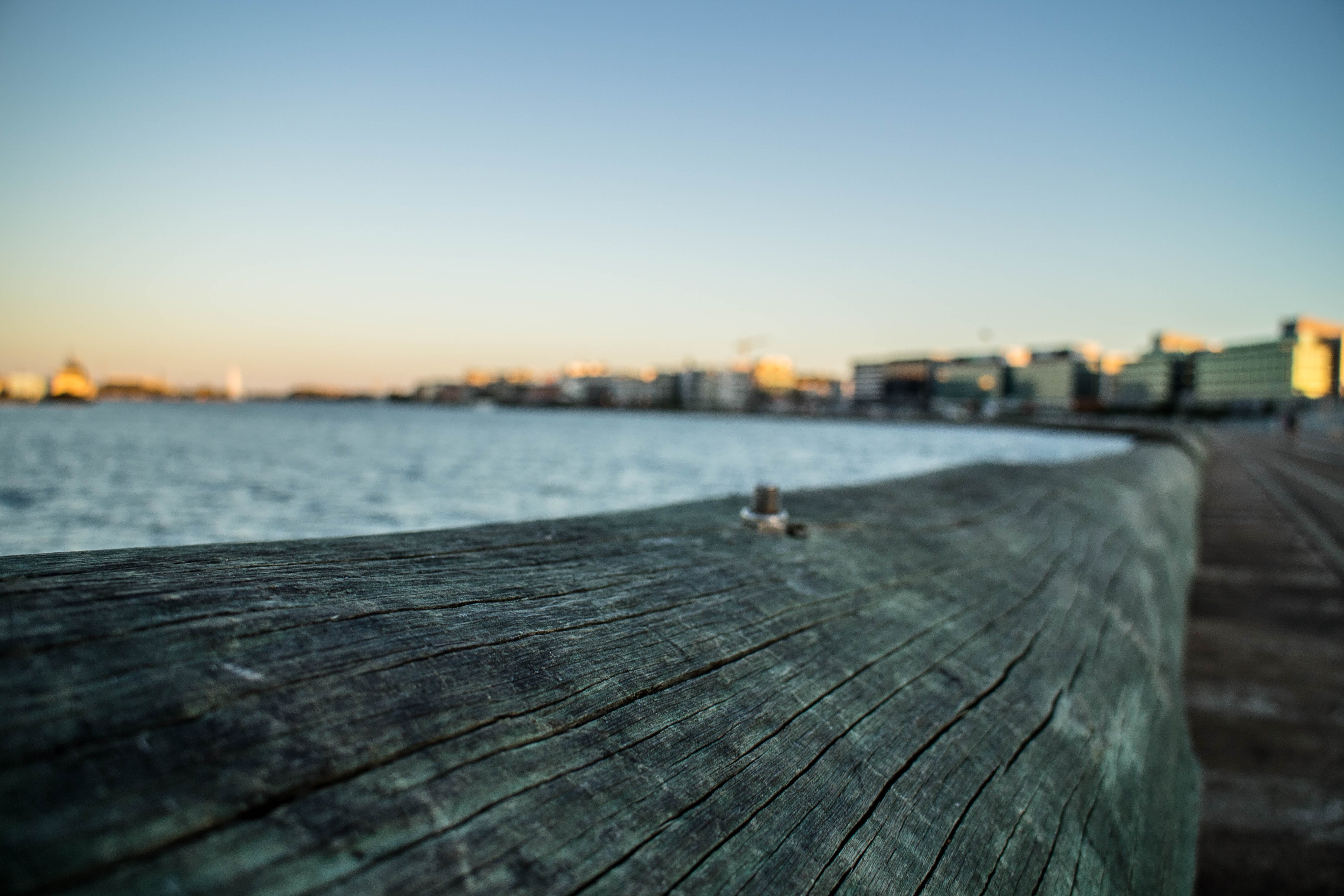 Brown Wooden Rails Overlooking City Skyline and Body of Water
