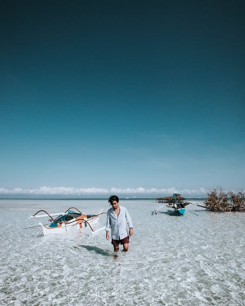 Photo of a Man Wearing White Top on the Beach