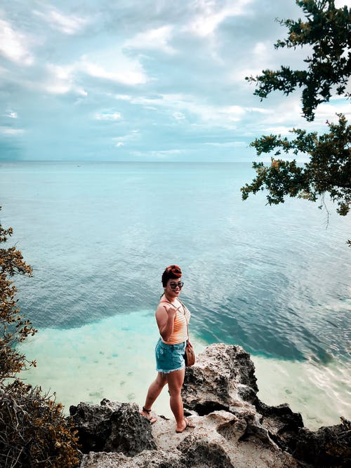 Photo of Smiling Woman in Blue Denim Shorts Standing on Seashore Rock Near Seashore
