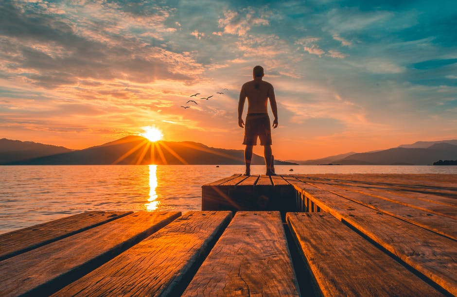 Photo of man standing on wooden planks near sea