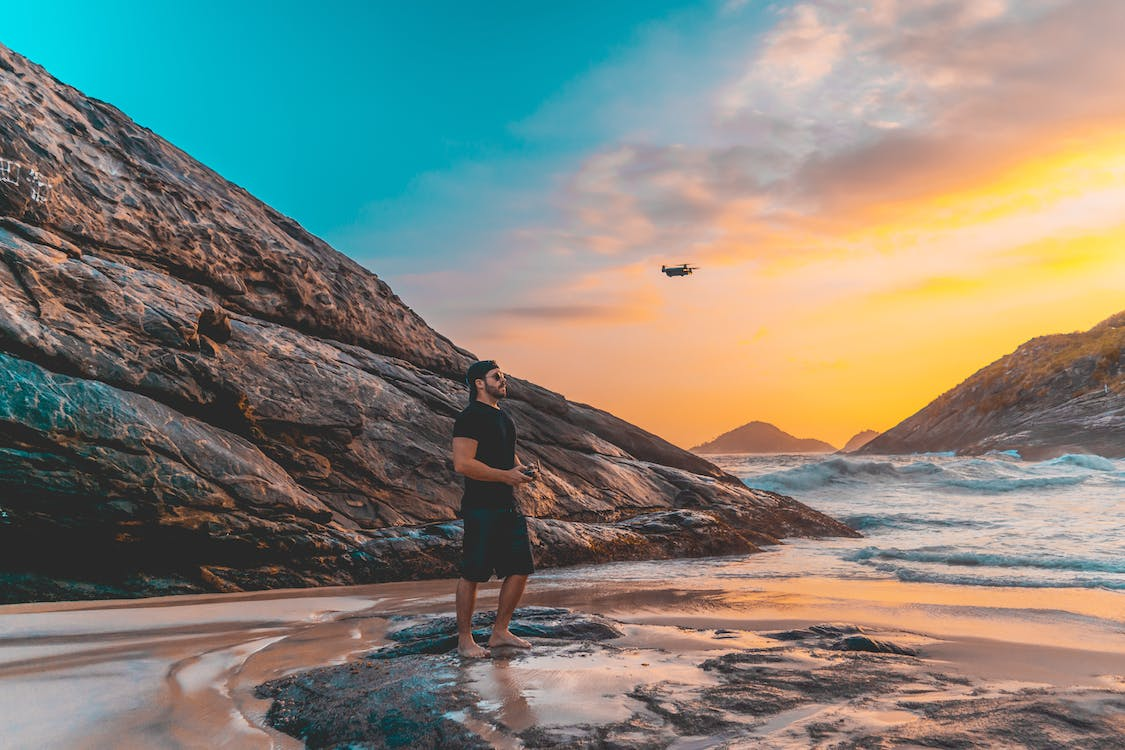 Man Standing on Rock Flying a Drone