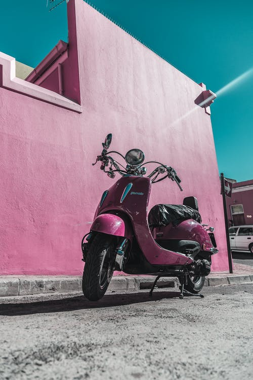 Photo of Pink Motor Scooter Parked Next to Pink Wall