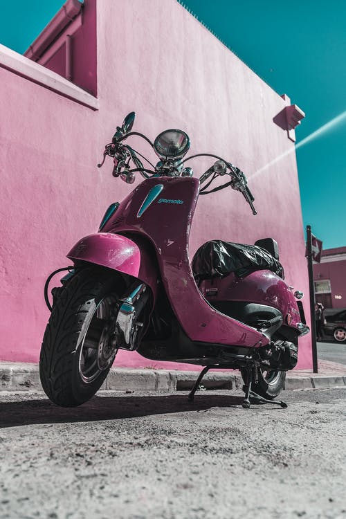 Pink Motor Scooter Parked Beside Pink Concrete Wall